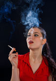 Woman with cigarette in cloud of smoke — Stock Photo