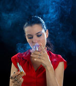 Woman with four cigarettes in cloud of smoke — Stock Photo