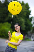 Girl with smiley balloon — Stock Photo