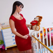 Pregnant woman near baby cradle — Stock Photo