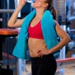 Woman in gym drinks water — Stok fotoğraf
