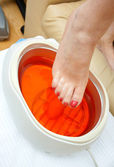 Woman foot in paraffin bath — Stock Photo
