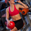 Woman in gym drinks water — Stock Photo #26330021