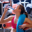 Woman in gym drinks water — Stockfoto