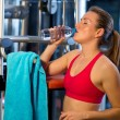 Woman in gym drinks water — Stock Photo #26331347