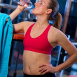 Woman in gym drinks water — Stock fotografie