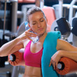 Woman in gym with water bottle — Stock Photo #26331739