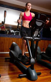 Woman in gym on stepper — Stock Photo