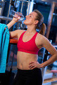 Woman in gym drinks water — Stock Photo