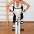 Fit woman on stationary bicycle in gym — Stock Photo