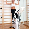 Fit woman working out on stationary bycicle — Stock Photo #26340911
