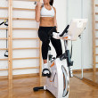 Fit woman working out on stationary bycicle — Stok fotoğraf
