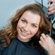 Woman curling hair in hairsalon — Stock fotografie