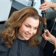 Woman curling hair in hairsalon — Stockfoto