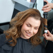Woman curling hair in hairsalon — Stok fotoğraf