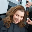 Woman curling hair in hairsalon — ストック写真