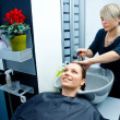 Hair stylist washing hair — Stockfoto