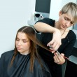 Hair stylist working on woman haircut — Stock Photo