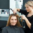 Foto Stock: Hair stylist curling woman hair in salon