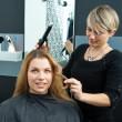 Hair stylist curling womhair in salon — Stockfoto #26346077