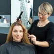 Foto Stock: Hair stylist curling womhair in salon