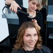 Hair stylist curling woman hair — Stock Photo #26346221