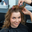 Hair stylist curling woman hair in salon — ストック写真