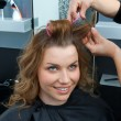 Hair stylist curling woman hair in salon — Stock fotografie