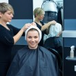 Hair stylist drying woman hair — Stock Photo