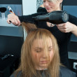Stock Photo: Hair stylist drying woman hair