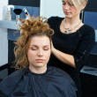 Stock Photo: Hair stylist curling womhair