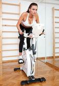 Fit žena na stacionárním kole v tělocvičně — Stock fotografie