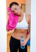 Woman in gym with water bottle — Stock Photo