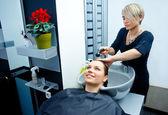 Hair stylist washing hair — Stock Photo