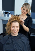 Hair stylist curling woman hair — Stock Photo