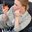 Woman putting some make up — Stockfoto