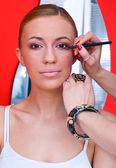 Woman putting on make up — Stock Photo