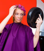 Woman with curlers and mirror — Stock Photo