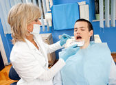 Woman dentist with male patient — Stock Photo