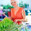 Woman on market place with vegetables — Stock Photo
