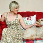 Woman and dog on sofa — Stock Photo #26581931
