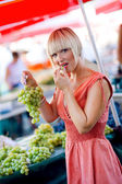 Woman tasting grapes in market — Stock Photo