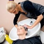 Stylist washing woman hair — Stock Photo #26591585