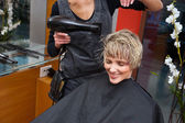 Stylist dryingwoman hair — Stock Photo