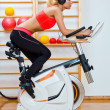 Woman on stationary speed bike — Stock Photo