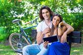 Mladý pár na lavičce v parku — Stock fotografie