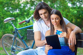 Young couple on the park bench with credit card and tablet — Stock Photo
