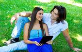 Tablet ile genç bir çift — Stok fotoğraf
