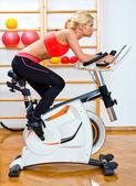 Mujer atractiva en bicicleta estacionaria — Foto de Stock