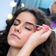 Woman putting mascara make up — Stockfoto